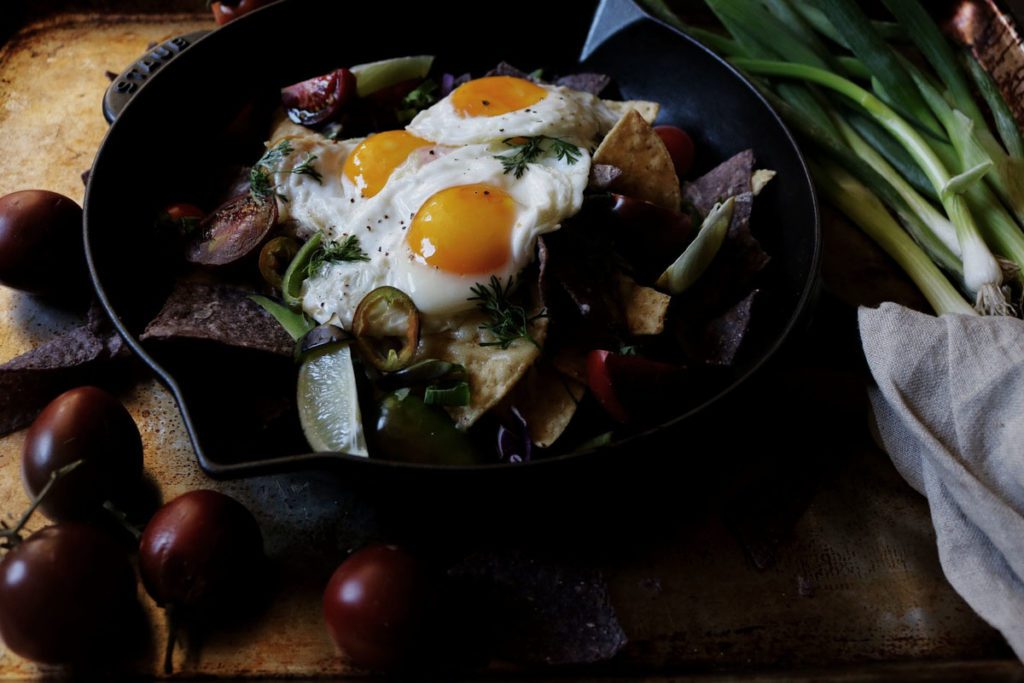 Breakfast Nachos | Recipe via DisplacedHousewife | A layer of tortilla chips, sharp white cheddar (but you can use yellow), thinly sliced fresno chilis, heirloom tomatoes, fresh-cut cilantro + an olive oil fried egg (OBSESSED)...yup, this is how we're doing breakfast. Mid-week. It's that fast and easy...not so much a recipe, but a guide to something really grub. That would be equally delicious for dinner or at 2am after the bars close. You decide! @displacedhousewife xo