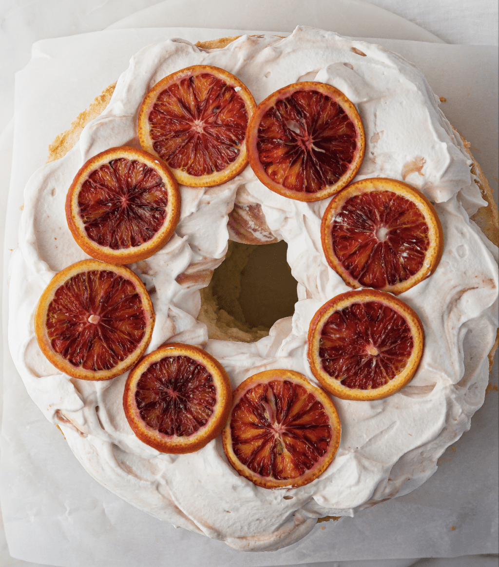 Round cake with white icing and slices of citrus on top