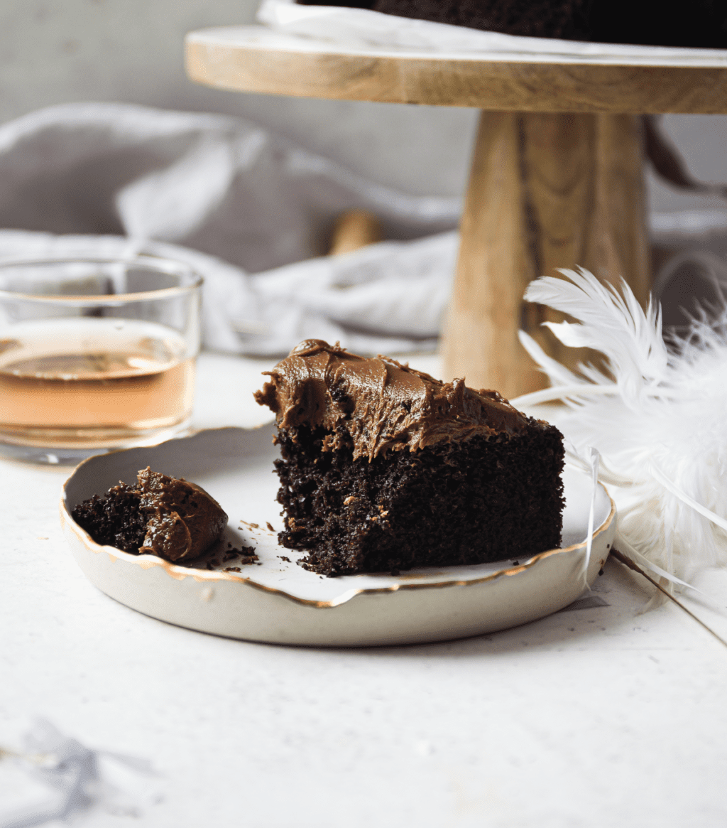 A slice of chocolate cake with chocolate icing on a white plate with a feather beside it