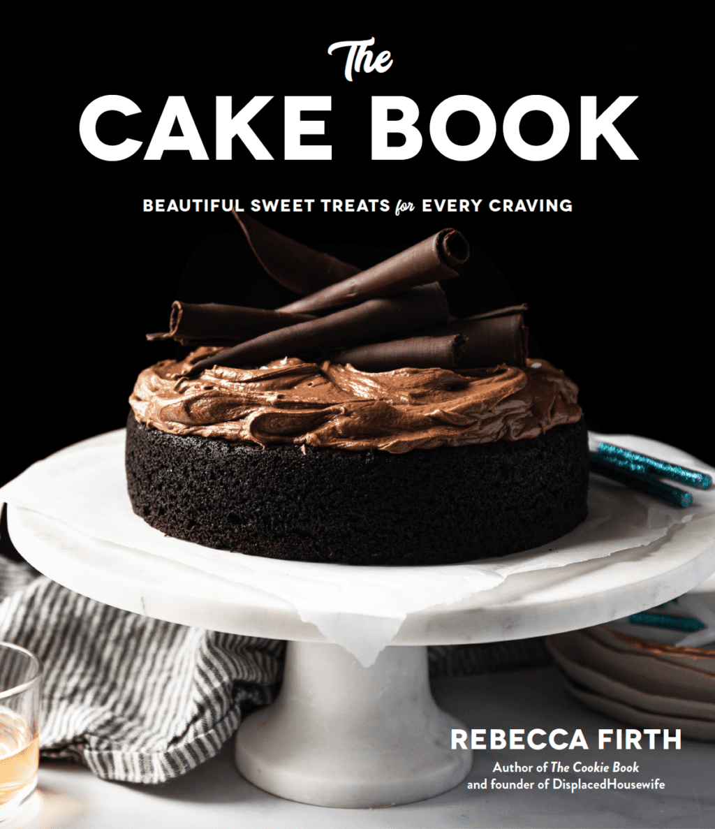 The Cake Book cover: Chocolate cake on a white cake stand on a black background
